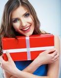 De jonge doos van de greep rode giet van de glimlachvrouw met wit lint. Royalty-vrije Stock Fotografie