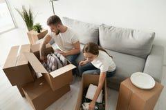 De jonge dozen van het paar uitpakkende karton met bezittingen stock foto's