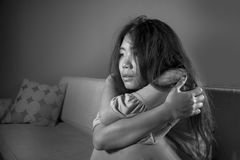 De jonge droevige en gedeprimeerde Aziatische Japanse laag die van de vrouwen thuis bank wanhopige en hulpeloze lijdende bezorgdh royalty-vrije stock fotografie