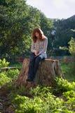 De jonge droevige melancholische vrouw zit op grote stomp stock afbeeldingen