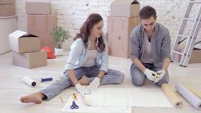 De jonge echtgenoot en de vrouw maken gemeten reparaties, en besnoeiingsbehang stock videobeelden