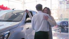 De jonge echtgenoot geeft gift aan mooie vrouw wat omhelzen en toont sleutels op het centrum van de autoverkoop stock video