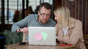 De jonge echtgenoten letten laptop op het scherm in koffie in open terras, het bespreken stock videobeelden