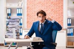 De jonge elegante man ongelukkig met teveel werk stock afbeelding