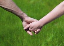 De jonge elkaars hand van de paargreep royalty-vrije stock foto