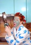 De jonge emotionele huisvrouw met rood haar in haarkrulspelden en met een kleimasker op een gezicht in woede dreigt, hebben bedre Stock Afbeelding