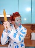 De jonge emotionele huisvrouw met rood haar, in haarkrulspelden, en met een kleimasker op een niet bevallen gezicht, bedreigt het Royalty-vrije Stock Foto