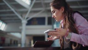 De jonge emotionele onderneemster in het roze overhemd en het zwarte sleeveless jasje is in het winkelcentrum Zij spreekt  stock videobeelden