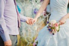 De jonge en gelukkige handen van de echtpaarholding romaans Stock Afbeelding