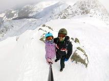 De jonge en gelukkige kerel en het meisje maken een foto met een zelf-stok plakken en smartphone op de piek van een sneeuw afgede royalty-vrije stock fotografie