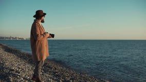 De jonge en modieuze fotograaf is dichtbij het overzees en veronderstelt hoe te fotograferen stock video