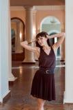 De jonge en mooie vrouw (meisje) in bruine kleding glimlacht in paleis Royalty-vrije Stock Afbeelding