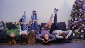 De jonge en onbezorgde meisjes ligt op bankbovenkant - neer en hebben pret stock videobeelden