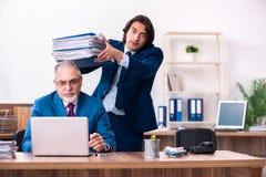 De jonge en oude werknemers die in het bureau samenwerken royalty-vrije stock foto's