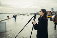 De jonge enthousiaste vrouwelijke driepoot van de de koolstofreis van de fotograafvestiging lichtgewicht voor zonsondergang/zonso royalty-vrije stock afbeeldingen
