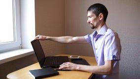De jonge ernstige kerel opent laptop en begint te werken stock videobeelden