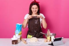 De jonge Europese prettige vrouw maakt foto van haar halve klaar pastei, post-it in sociaal netwerkenplaatsen Vrolijke aantrekkel stock afbeelding