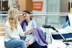 De jonge Europese vrolijke paar of vriendenvrouwen met zuigeling is sittin stock afbeelding