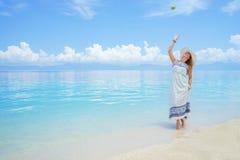 De jonge europian vrouw in lichte kleding en hoed loopt bij het witte overzeese van het zandstrand dichtbij kalme verbazende spel Royalty-vrije Stock Afbeelding