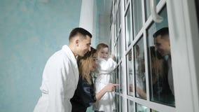 De jonge familie bekijkt grappig iets venster stock footage