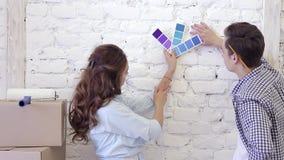 De jonge familie bespreekt de reparatie van flat, kiest kleuren van de steekproeven stock video
