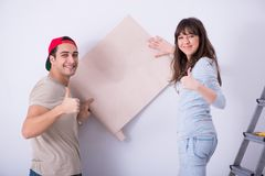 De jonge familie die vernieuwing thuis met nieuw behang doen stock foto