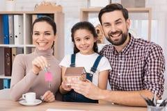 De jonge familie is gelukkig om nieuw huis, houdend sleutels van huis en miniatuurhuis te kopen royalty-vrije stock foto's