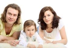De jonge familie ligt op witte pluizig stock afbeeldingen