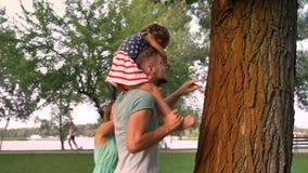 De jonge familie loopt in park in de zomer, zit het meisje op vader` s schouders en plukt blad stock video