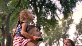 De jonge familie loopt in park in de zomer, zit het meisje op vader` s schouders en zij letten omhoog op bij bomen stock video