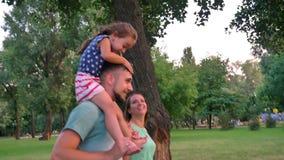 De jonge familie loopt in park in de zomer, zit het meisje op vader` s schouders, zonsondergang, zijaanzicht stock video