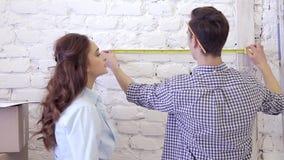 De jonge familie meet de afmetingen van de muur met een meetlint stock footage