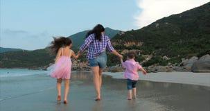 De jonge familie, de moeder en de kinderen lopen langs de kust Gelukkige familie die op overzeese kust lopen stock video