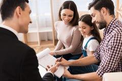 De jonge familie ondertekent partnerovereenkomst om huis samen met makelaar in onroerend goed te kopen stock foto