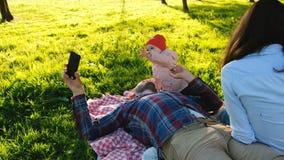 De jonge familie rust op aard, vraagt een klein kind om een smartphone, haalt de vader de telefoon van de baby weg royalty-vrije stock afbeeldingen