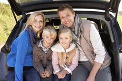De jonge familie stelt samen bij achtergedeelte van auto Stock Foto's