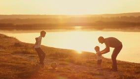 De jonge familie stoeide samen om voetbalvoetbal op het strand bij zonsondergang te spelen stock video