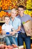 De jonge familie tegen planken van vruchten gaat winkelend Stock Afbeelding