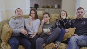 De jonge film van vriendenhorloges thuis stock video