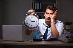 De jonge financiële manager die laat bij nacht in bureau werken royalty-vrije stock afbeelding