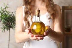 De jonge fles van de vrouwenholding verse olijfolie Royalty-vrije Stock Afbeeldingen