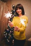 De jonge fonkelingen van de vrouwenholding in haar handen dichtbij Kerstmisboom Stock Foto