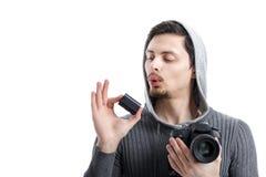De jonge fotograaf houdt de batterij voor de digitale camera van DSLR Stock Afbeeldingen