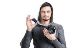 De jonge fotograaf houdt de batterij voor DSLR de digitale camera is Royalty-vrije Stock Foto