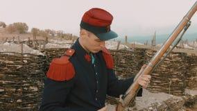 De jonge Franse militair maakt het jachtgeweer vóór het schot schoon stock videobeelden