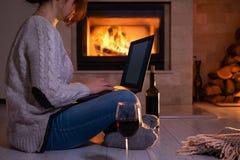 De jonge freelancervrouw zit bij de vloer met laptop stock fotografie