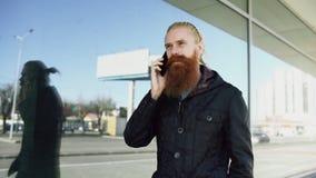 De jonge gebaarde hipstermens concentreerde het spreken op telefoon op citystreet en heeft gesprek dichtbij de bureaubouw Royalty-vrije Stock Afbeelding