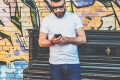De jonge gebaarde hipstermens gekleed in witte t-shirt en zonnebril is tribunes tegen muur met graffiti stock afbeeldingen