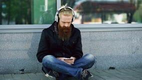 De jonge gebaarde hipstermens met hoofdtelefoons die op weg zitten en smartphone gebruiken voor luistert aan muziek en Internet-h Royalty-vrije Stock Foto's