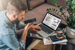 De jonge gebaarde hipstermens, ondernemer zit op laag bij koffietafel, gebruikt laptop met grafieken, in kaart brengt op het sche royalty-vrije stock foto